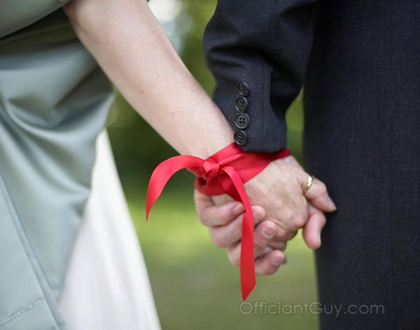 a couple holding hands after a handfasting wedding ceremony that this officiant can perform