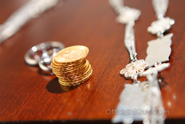thirteen coins with wedding rings symbolizing a coin wedding ceremony